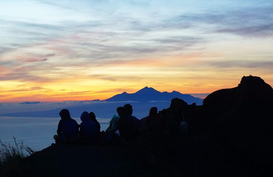 Silhouetted group sitting on Bali mountain top at sunrise