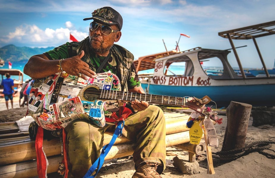 A local plays a battered old guitar on the sea front of Gili Air