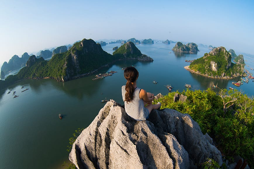 A young traveler girl sit on the top of mountain in Halong bay and enjoy the beauty of seascape. Young girl love wild life, travel, freedom.;